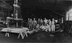 Standing third from left, James (Speedy) Blalock, Nat Cox, Sam Jarrett, far right John Baker standing and Milton Hill kneeling. The furnace and spout can be seen in the distant left behind the portable rack and men.